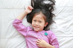 Happy little Asian child girl lying on white blanket on bed with looking at camera. Above view stock photo