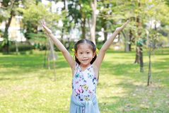 Happy little Asian child girl opened her hands in the summer park stock photo