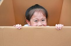 Happy little Asian child girl playing peekaboo and lie in big cardboard box.  stock images