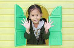 Happy little Asian child girl playing with window toy playhouse in playground stock photography