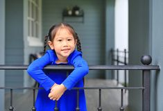 Happy little Asian child girl standing at house balcony bars and looking camera at the morning royalty free stock photos