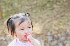 Happy Little asian girl eating jelly strawberry in the park. Happy Little asian girl eating jelly strawberry Royalty Free Stock Images