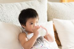 Happy little asian girl hand holding drinking milk glass Royalty Free Stock Photography
