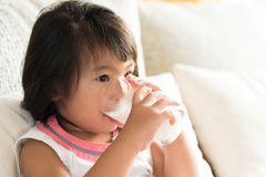 Happy little asian girl hand holding drinking milk glass, sitting on sofa at home. Medicine and health care concept. royalty free stock photography