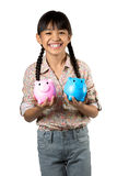 Happy little asian girl with piggy bank Stock Images