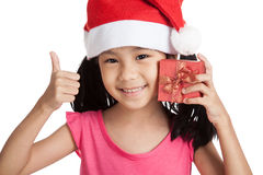 Happy little asian girl show thumbs up with santa hat and gift b Royalty Free Stock Image