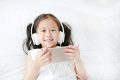 Happy little Asian girl using headphones listen music by smartphone smiling and looking camera while lying on bed at home royalty free stock photography