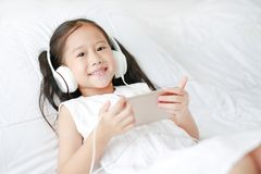 Happy little Asian girl using headphones listen music by smartphone smiling and looking camera while lying on bed at home royalty free stock photos