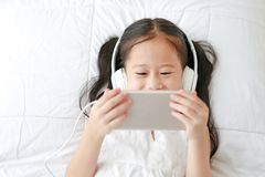 Happy little Asian girl using headphones listen music by smartphone smiling while lying on bed at home.  stock image