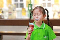 Happy little Asian kid girl enjoy eating ice cream cone with stains around her mouth stock image