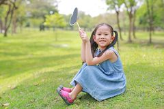 Happy little Asian kid girl holding blank heart label sitting on green grass at garden outdoor royalty free stock photography
