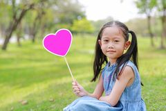 Happy little Asian kid girl holding blank heart label sitting on green grass at garden outdoor stock photos