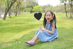 Happy little Asian kid girl holding blank heart label sitting on green grass at garden outdoor.  royalty free stock image