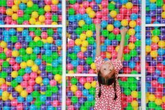 Happy little Asian kid girl playing climb and hanging on cage of playground colorful toy ball with looking camera.  stock photography