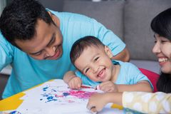 Asian kid painting and drawing. Happy little asian kid painting and drawing at home using water color paint Stock Photo