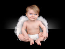 Happy Little Baby Angel with wings. A little baby is isolated on a black background and smiling with white angel wings stock image