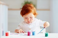 Happy little baby artist drawing with colorful paints at home Royalty Free Stock Image
