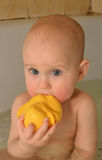 Happy little baby is bathed in the bath with duck. Funny cute baby taking a bath with toys. he likes to splash in the water. little smiling baby. his face lit Royalty Free Stock Photography