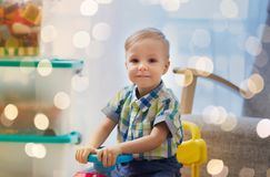 Happy little baby boy driving ride-on car at home. Childhood, toys and people concept - happy little baby boy driving ride-on toy car at home Royalty Free Stock Photos