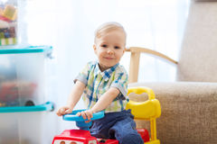 Happy little baby boy driving ride-on car at home. Childhood, toys and people concept - happy little baby boy driving ride-on toy car at home Royalty Free Stock Photography