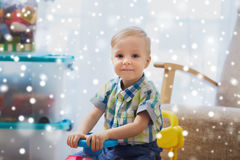 Happy little baby boy driving ride-on car at home. Childhood, toys and people concept - happy little baby boy driving ride-on toy car at home over snow Royalty Free Stock Photo