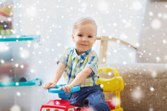 Happy little baby boy driving ride-on car at home Stock Photography