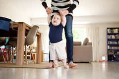 Happy little baby boy learning to walk with mother help at home. Portrait of happy little baby boy learning to walk with mother help at home stock photos