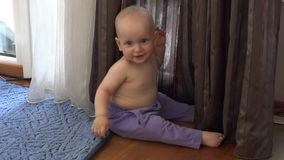 Happy little baby boy in pants play near curtain. Smiling boy looking at camera stock video