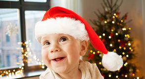 Happy little baby boy in santa hat on christmas stock image