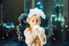 Happy little baby boy sitting in bath tub in the evening before going to sleep on the background of a window overlooking. The evening city. Portrait of baby royalty free stock images