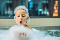 Happy little baby boy sitting in bath tub in the evening before going to sleep on the background of a window overlooking. The evening city. Portrait of baby stock photos