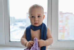 Happy little baby boy standing near the window weared in winter hat and scarf, city at background royalty free stock photo