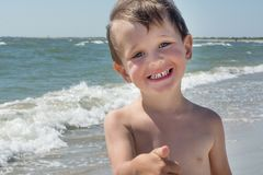 Happy little baby boy stands against the sea and laughs, happy baby. Royalty Free Stock Images