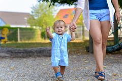 Happy little baby boy walking with his mother. Or babysitter outdoors in a playground in a low angle view of him waving at the camera stock photos