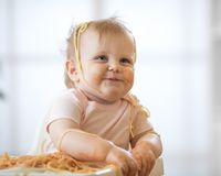 Happy little baby girl eating spaghetti. Happy little baby child girl eating spaghetti Royalty Free Stock Images