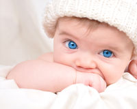Happy Little Baby Child Sucking Hand. A young child is looking into the camera and sucking their hand. The baby is wearing a hat and has bright blue eyes Royalty Free Stock Images