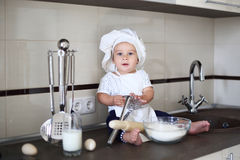 Happy little baby in a cook cap laughs Stock Photography