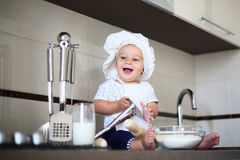 Happy little baby in a cook cap laughs Royalty Free Stock Images