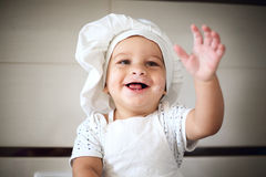 Happy little baby in a cook cap laughs Royalty Free Stock Photos