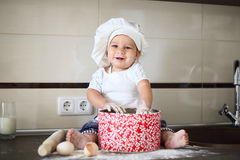 Happy little baby in a cook cap laughs Royalty Free Stock Photography