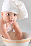 Happy little baby in a cook cap laughs Stock Images