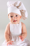 Happy little baby in a cook cap laughs Stock Photos