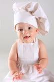 Happy little baby in a cook cap laughs. Happy cute little baby in a cook cap laughs Stock Photos