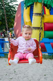 Happy little baby girl with a beautiful clasp on his head and jacket riding on a chain swing in amusement park Stock Photography