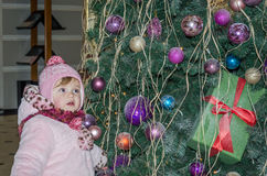 Happy little baby girl is beautiful in a white fur coat, hat, scarf near a Christmas tree decorated with toys and garlands and smi Royalty Free Stock Photos