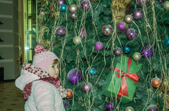 Happy little baby girl is beautiful in a white fur coat, hat, scarf near a Christmas tree decorated with toys and garlands and smi Royalty Free Stock Photo