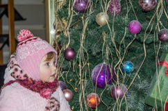 Happy little baby girl is beautiful in a white fur coat, hat, scarf near a Christmas tree decorated with toys and garlands and smi Royalty Free Stock Photography