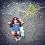 Happy little baby girl. Cute little baby girl having fun outdoors, drawing on asphalt sun and tanning under it, happy childhood in summer camp, active summertime royalty free stock photography