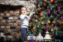 Happy little baby girl decorating christmas tree with toys on holidays Stock Image
