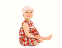 Happy little baby girl in the dress sitting on a whi Royalty Free Stock Photos